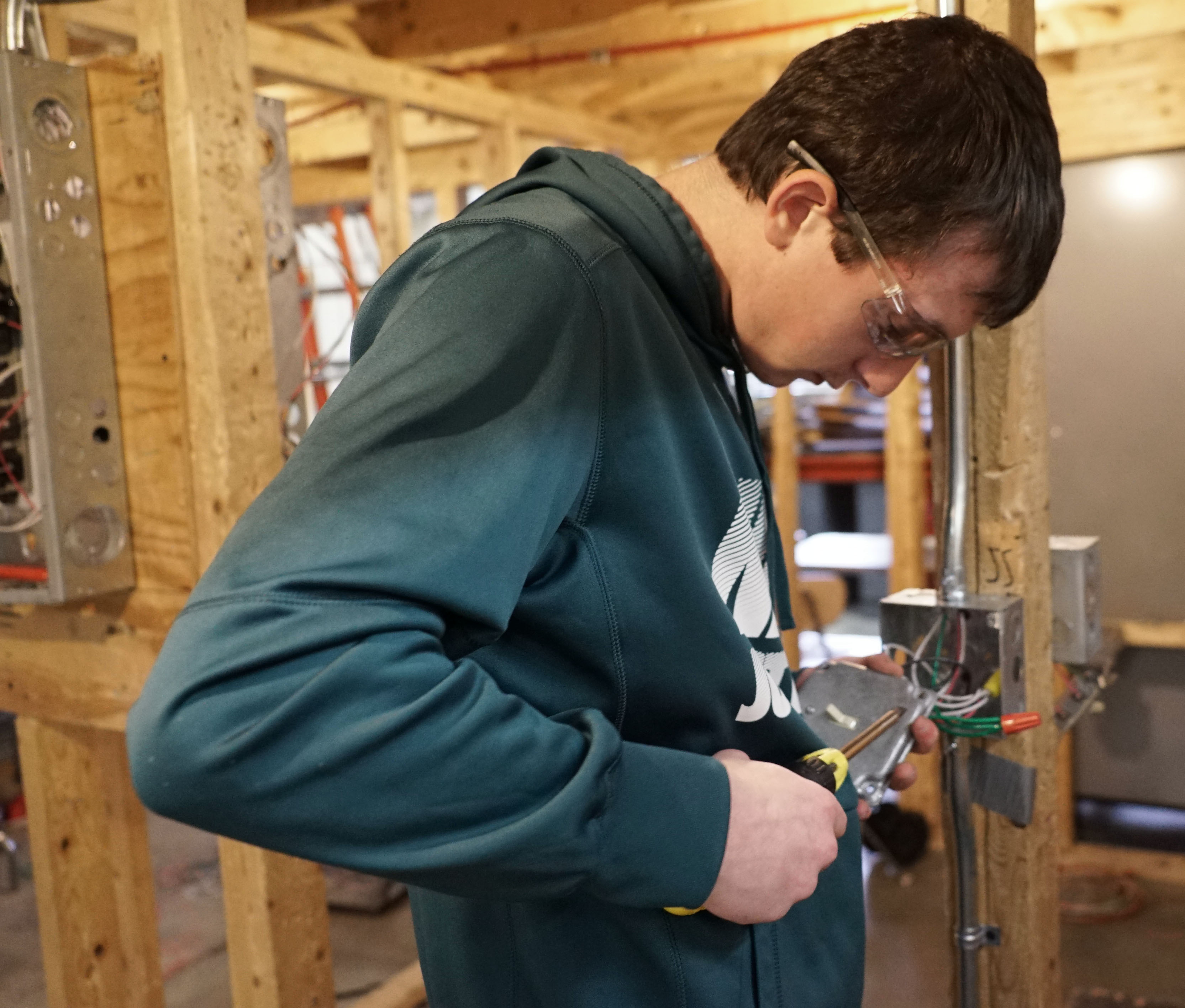 student working on electrical outlet