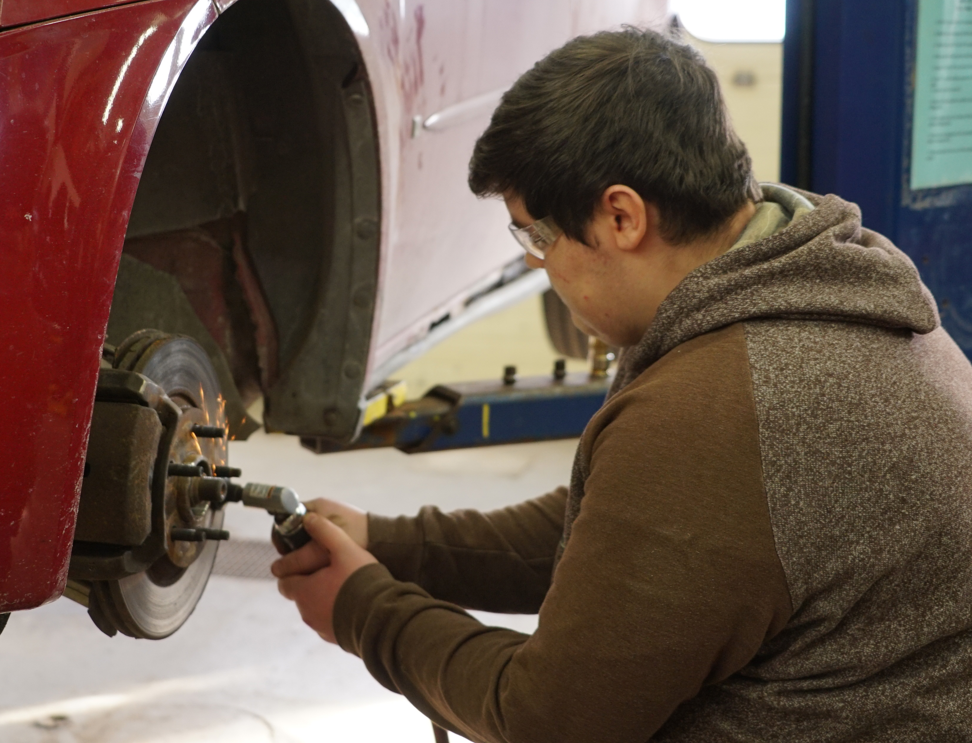 student works on car's brakes